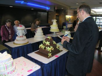 A judge scrutinizes an entry in the wedding cake competition while spectators look on.